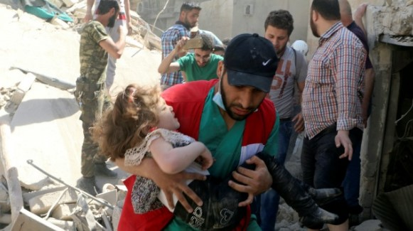 A civil defence member carries a child that survived from under the rubble at a site hit by airstrikes in the rebel held area of Old Aleppo, Syria, April 28, 2016. Picture Courtesy: Reuters
